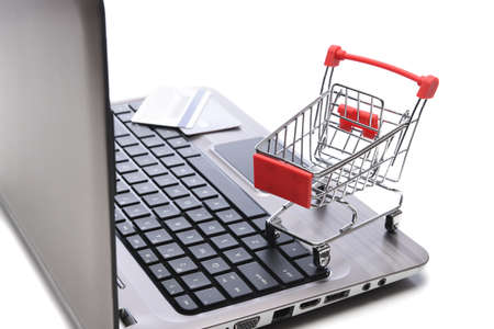 Internet, technology, ecommerce and online payment concept. Closeup of a shopping cart and credit cards on the keyboard of an open laptop computer.