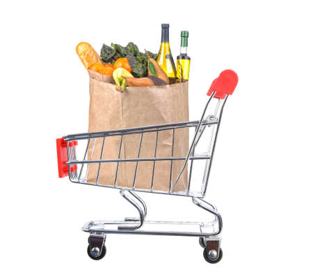 A brown paper bag filled with food in a grocery store shopping cart. Isolated on white.