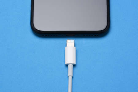 Closeup of a charging cord and smartphone on a blue background.