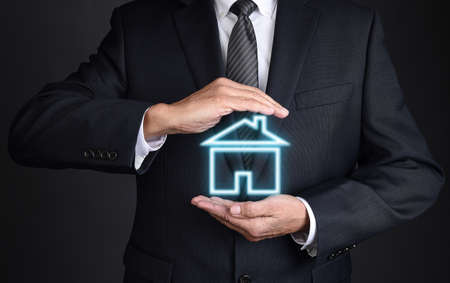 Real Estate Concept. Closeup of an unrecognizable Realtor with cupped hands around a glowing house shape.