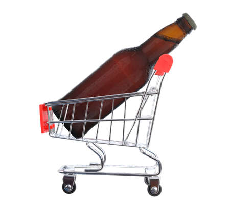 A brown beer bottle inside a grocery store shopping cart, isolated on white. Stockfoto