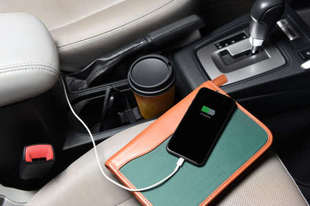 A businessman cell phone on the passenger seat and plugged into the cars charging port with coffee cup, and notebook. Stockfoto