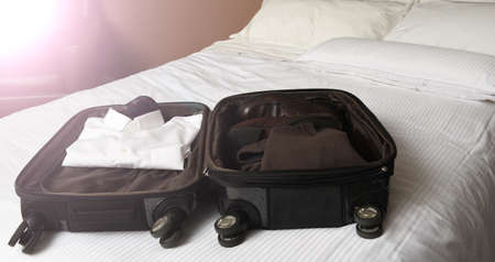 A businessman's open suitcase on top pof a hotel bed with intentional flare from a window.