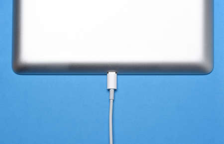 Closeup of a charging cord and Tablet Computer on a blue background. Stockfoto - 163474495