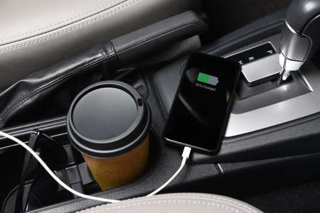 A SmartPhone plugged in the charging port on the console of a modern automobile, closeup with coffee cup and sunglasses.