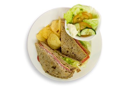 cheese plate: a triple decker hearty sandwich with vegetables and chips from top view