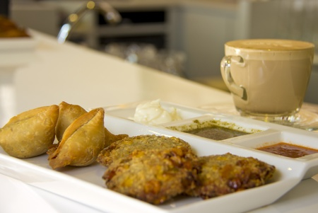 Samosa and croquets stuffed with potatoes and vegetables with coffee on the background photo