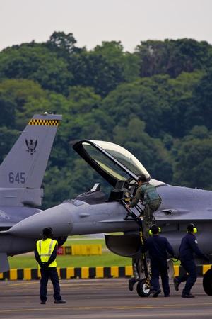 pilotos aviadores: Piloto está recibiendo salto listo a su cabina victimizar con ayuda de su tripulación aérea Foto de archivo