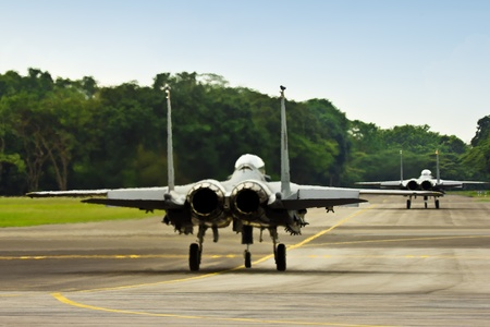 f 15: Two fighter jets, F15 & F16 taxiing down to runway to take-off