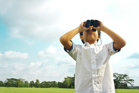 A young boy is observing with binoculars in outdoor nature