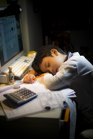 A boy fell asleep tired during his study