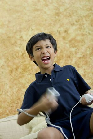 wii: A young boy playing video game in excitement
