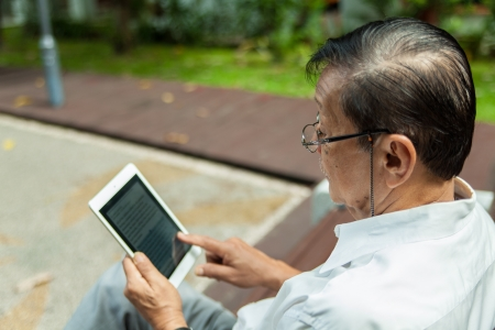 An old man enjoying morning sun reading newspaper from an iPad  photo