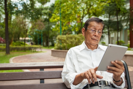 An old man enjoying morning sun reading newspaper from an iPad