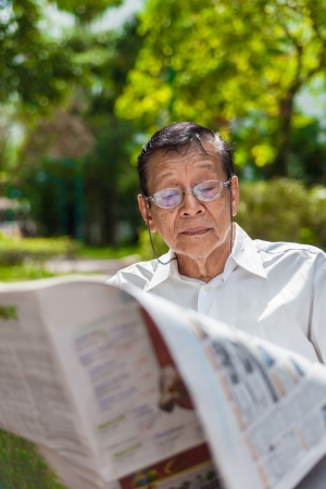 An old man enjoying morning sun reading newspaper