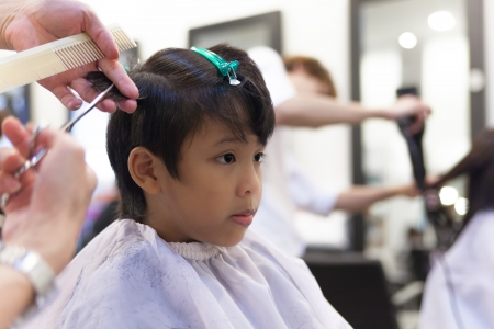 A young boy getting haircut in fancy hair salon