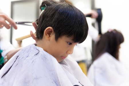 first job: A young boy getting haircut in fancy hair salon