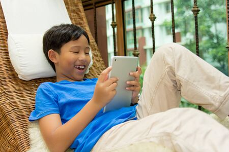 Child Playing with Digital Tablet Indoor