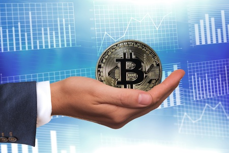 Bitcoin on mans hand on blue graphic background
