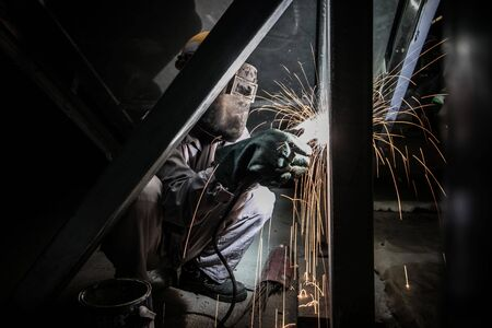 Industrial factory worker working welding metal with sparks