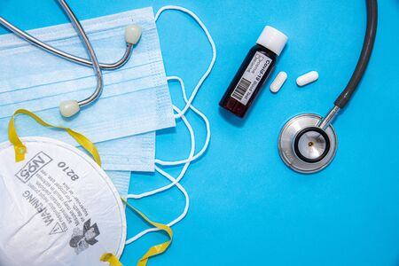 Concept of Coronavirus or Covid-19 pandemic to use as background with blue colour and medical blood test, stethoscope, mask, thermometer, gloves, syringe, pill tablet medicines