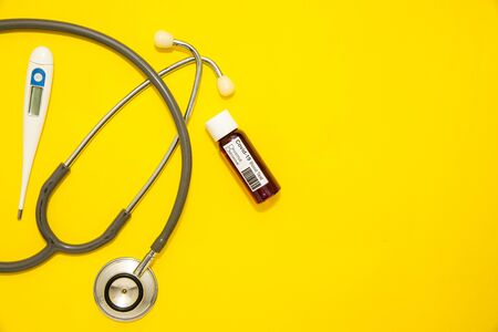Concept of Coronavirus or Covid-19 pandemic to use as background with yellow colour and medical blood test, stethoscope, thermometer Stok Fotoğraf