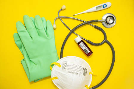 Concept of Coronavirus or Covid-19 pandemic to use as background with yellow colour and medical blood test, stethoscope, thermometer, gloves, N95 surgical mask
