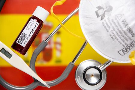 Concept of Coronavirus or Covid-19 pandemic to use as background with Spain Spanish country flag and medical blood test, stethoscope, surgical N95 mask, thermometer