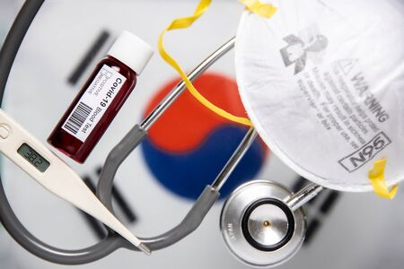 Concept of Coronavirus or Covid-19 pandemic to use as background with South Korea Korean country flag and medical blood test, stethoscope, surgical N95 mask, thermometer