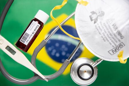 Concept of Coronavirus or Covid-19 pandemic to use as background with Brazil Brazilian Brasil country flag and medical blood test, stethoscope, surgical N95 mask, thermometer