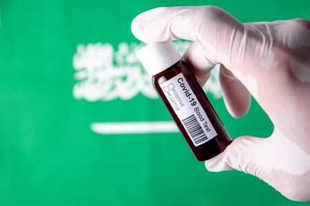 Concept of Coronavirus or Covid-19 pandemic to use as background with Saudi Arabia Arab Arabian country flag and medical blood test Stok Fotoğraf