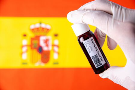 Concept of Coronavirus or Covid-19 pandemic to use as background with Spain Spanish country flag and medical blood test Stok Fotoğraf