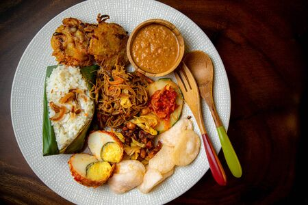 Asia Asian Indonesian Malaysia Singapore Traditional Food nasi uduk or nasi lemak coconut rice with chicken, noodle, eggs, cracker, vegetable fritters