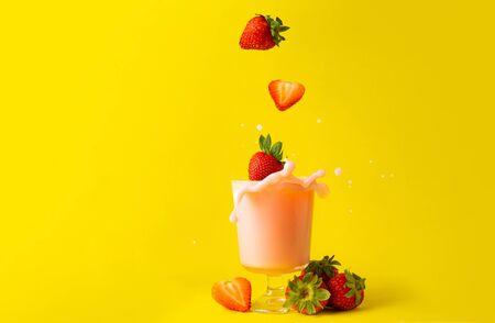 splashing splash strawberry juice smoothies and strawberries on yellow background as healthy detox diet drinks Stok Fotoğraf