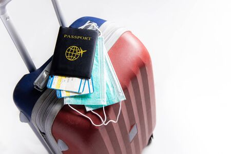 Travel suitcase / luggage, passport, air ticket and mask. Travel ban during the pandemic of  coronavirus or covid-19