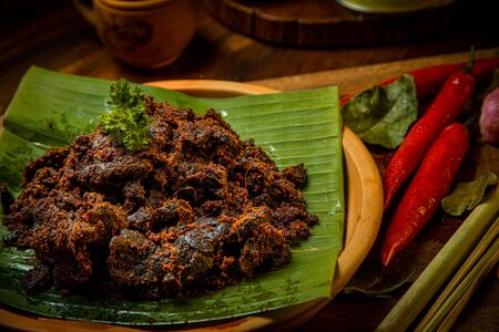 Rendang Paru or Spicy Beef Lung stew traditional food from Padang, Indonesia. The dish is arranged among the spices and herbs used in the original recipe like chili, lemongrass onion