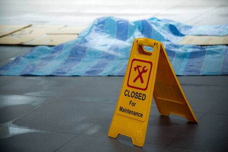 Yellow closed for maintenance sign during rain with puddle of water when floor is slippery and copy space for text