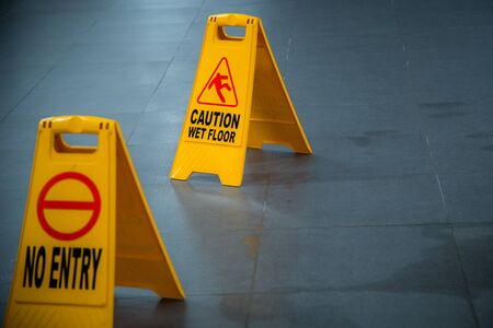 Yellow wet floor caution sign during rain with puddle of water when floor is slippery and copy space for text