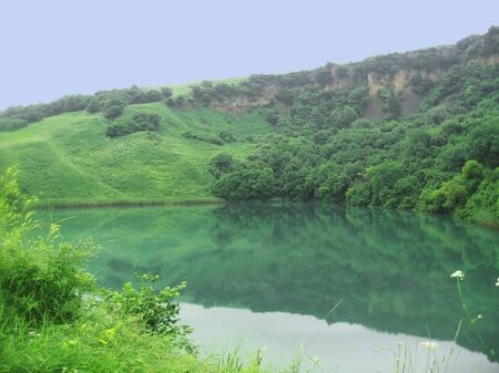 Small lake between the caucasus mountains summertime photo