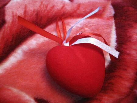 Red heart with red and white stripes on the pink background photo