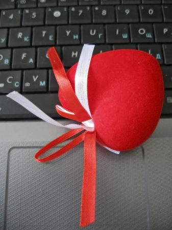 Red heart laying on the keyboard of notebook photo