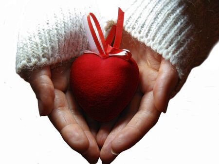 Red heart with red and white stripes on woman hands on the white baclkground