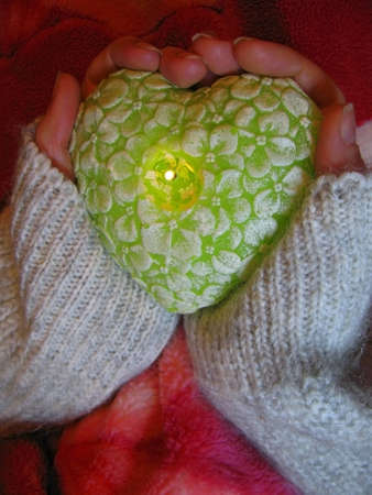 Valentine heart and heart shape candle in woman hands photo