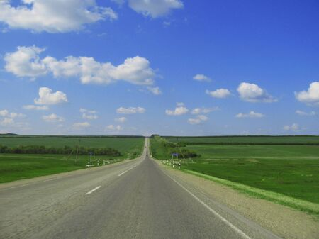 Wide highway and meadow  Clouds over and blue sky Stock Photo - 13884370