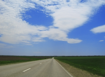 Wide highway and meadow  Clouds over and blue sky Stock Photo