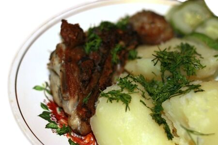 Fried meat and bolied potatoes and dill over isolated photo