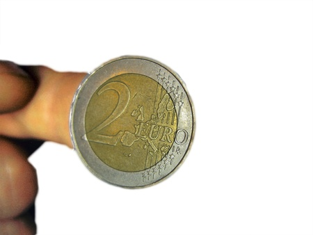 Two euro coin on the male fingers isolated photo