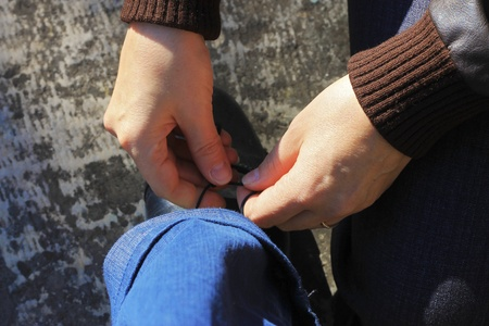 Woman tying a shoelaces on the mans shoes photo
