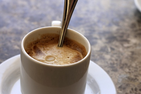 White cup of coffee with a spoon photo