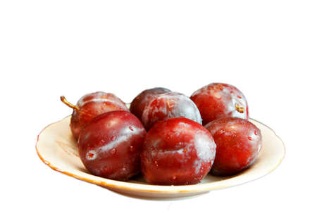 Fresh Ripe Black Plums In A White Plate Isolated On White Background photo